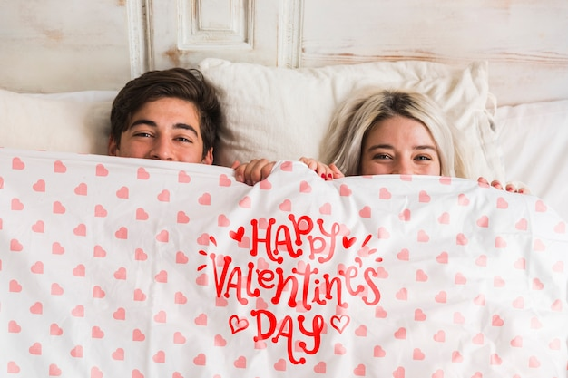 Cute young couple in bed for valentines day Free Psd