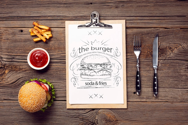 Cutlery and burger with fries menu on wooden background Free Psd
