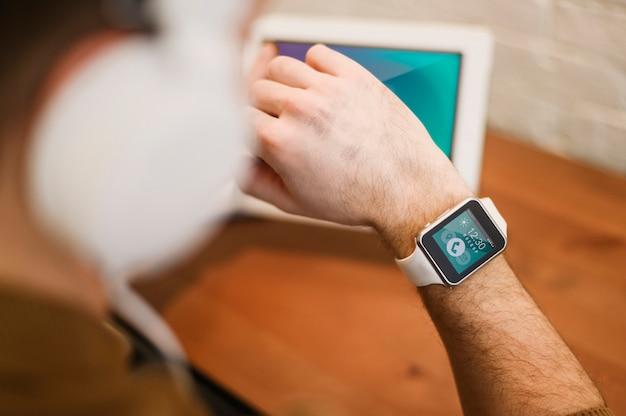 Расфокусированным человек, работающий из дома, глядя на smartwatch Бесплатные Psd