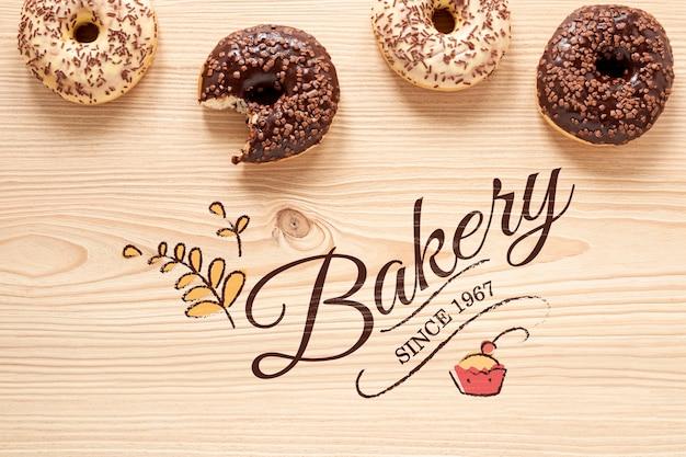 Вкусные пончики на деревянный стол макет Бесплатные Psd