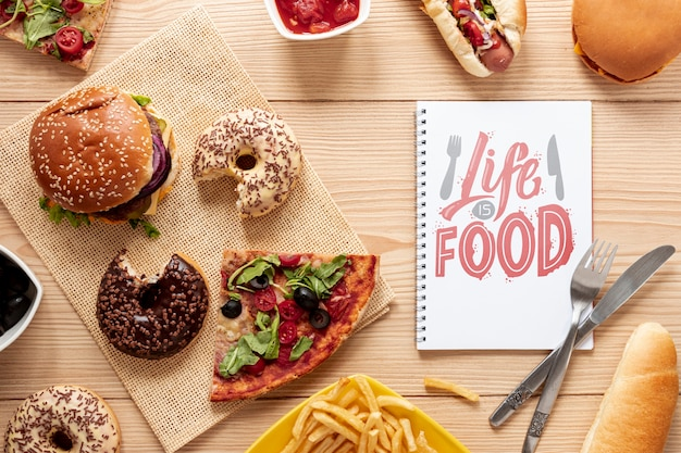 Delicious fast food on wooden table with notebook mock-up Free Psd
