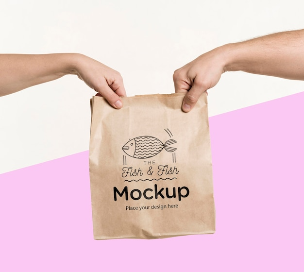 Delivery man handing a bag of food to a client with mock-up Free Psd