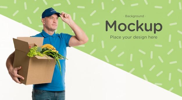 Доставщик, держащий коробку овощей Бесплатные Psd