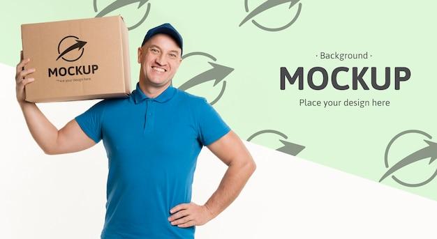 背景のモックアップで彼の肩に箱を抱えて配達人 無料 Psd