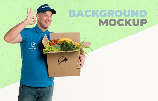 Delivery man holding a box full of vegetables mock-up Free Psd