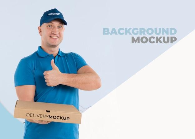 Uomo di consegna che tiene una scatola con pizza Psd Gratuite