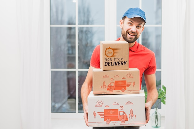 Delivery mockup with man holding boxes Free Psd