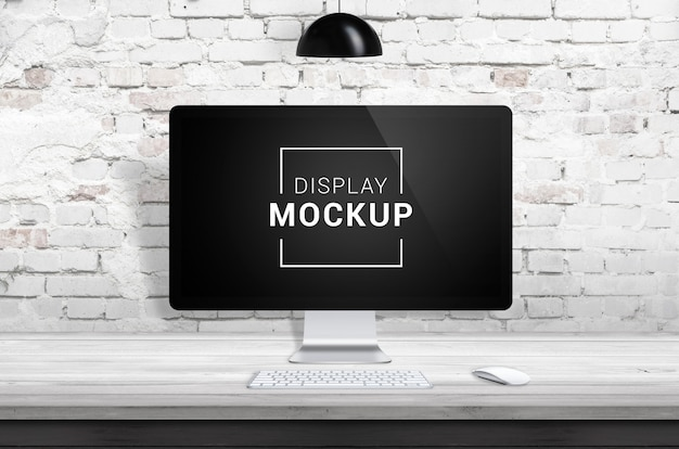 Display mockup on wooden desk with brick wall Premium Psd