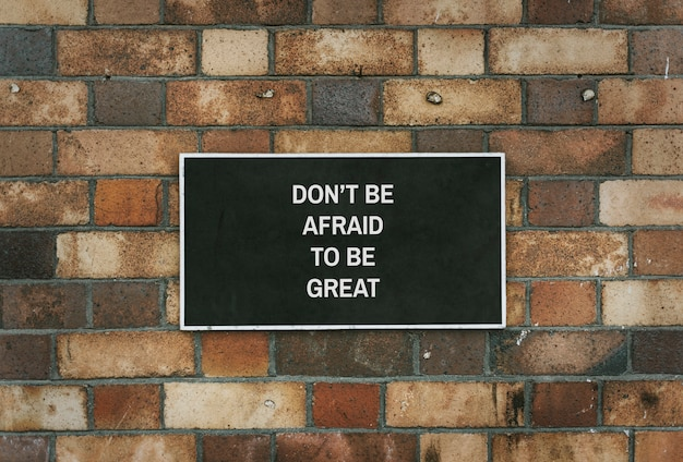 Don' be afraid to be great board mockup on a brick wall Free Psd