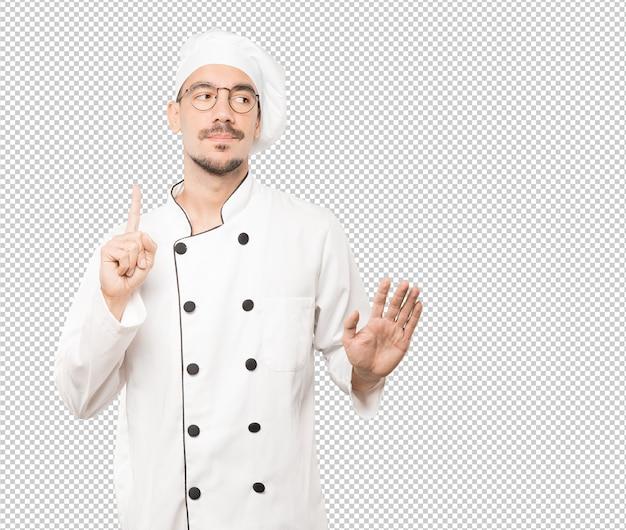 Сомнительный молодой шеф-повар делает жест спокойствия Premium Psd