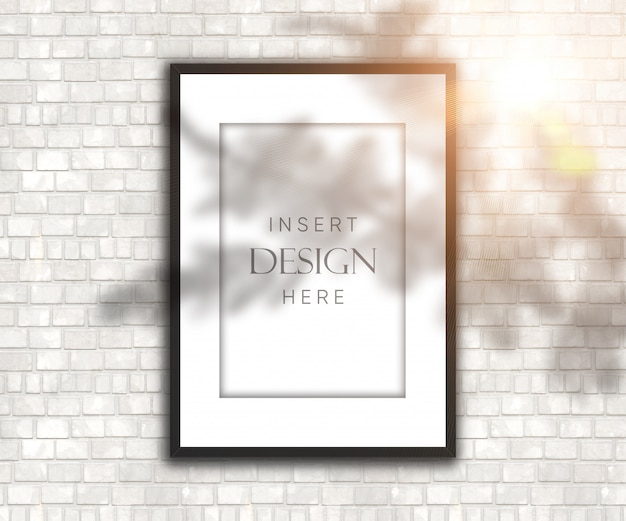 Editable blank picture frame on brick wall with shadow and sunshine overlay Free Psd