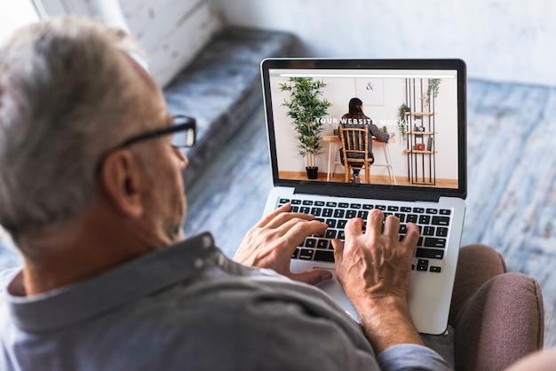 Elderly man using laptop Free Psd