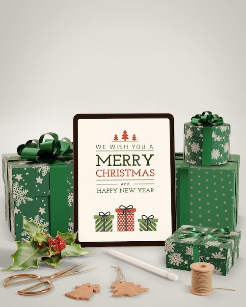 Electronic tablet beside gifts for christmas Free Psd