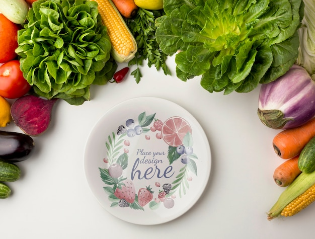 Empty plate mock-up with frame made from delicious fresh veggies Free Psd