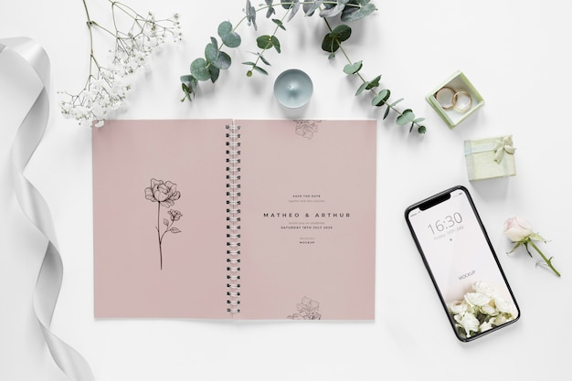 Fat lay of wedding notebook with smartphone and plants Free Psd