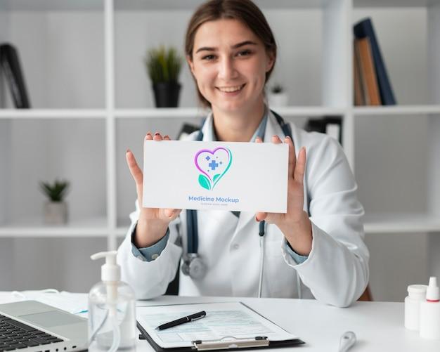Dottoressa in possesso di una scheda mock-up Psd Gratuite