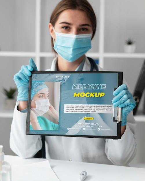 Medico femminile che tiene una lavagna per appunti di mock-up Psd Gratuite