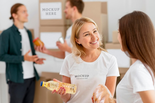 Женщины-волонтеры готовят коробки для пожертвований, а мужчина жертвует еду Premium Psd