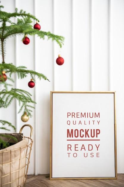Festive golden frame by a christmas tree Free Psd