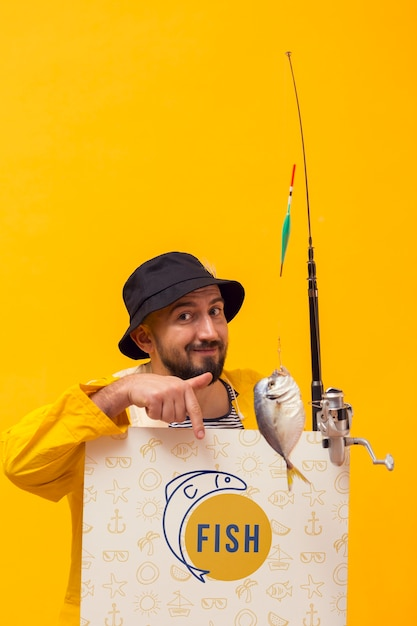 魚とロッドを保持しているレインコートの漁師 無料 Psd