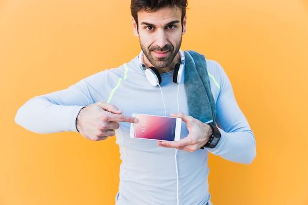 Фитнес-макет с человеком, показывающим смартфон Бесплатные Psd
