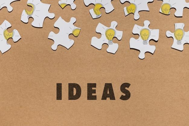 Плоская планировка с кусочками головоломки на коричневом фоне Бесплатные Psd