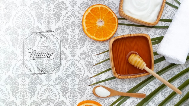 Flat lay of body butter and honey with orange slice Free Psd