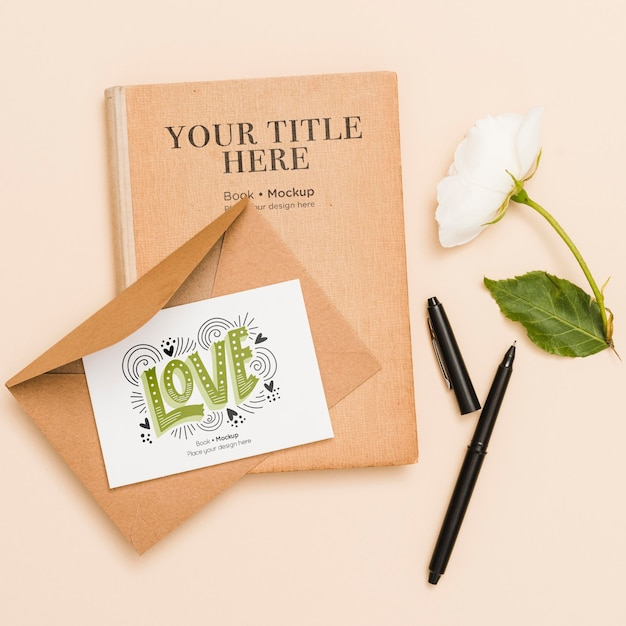 Flat lay of book with flower and card Free Psd