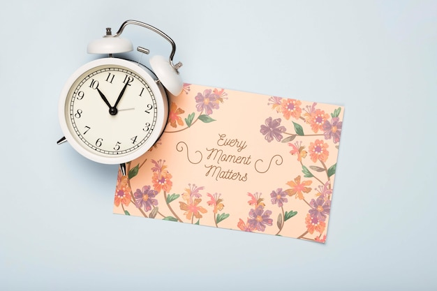 Flat lay of clock and floral card for spring Free Psd