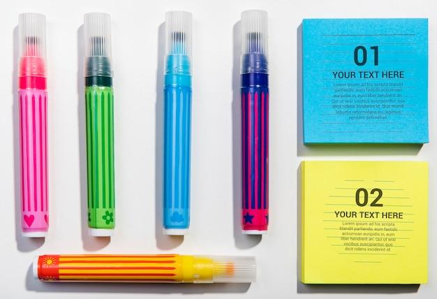 Плоская раскладка красочных маркеров и блокнотных нотных блоков. Бесплатные Psd