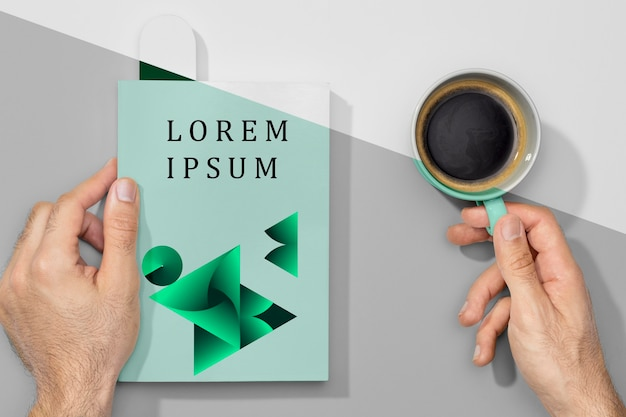Flat lay hands holding book mock-up and coffee Free Psd