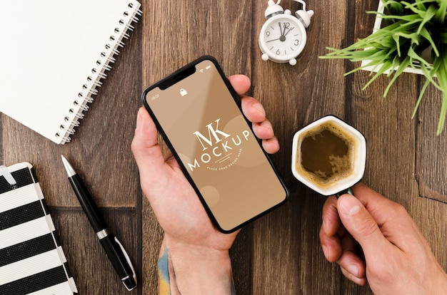 Flat lay hands holding smartphone mock-up and coffee Free Psd