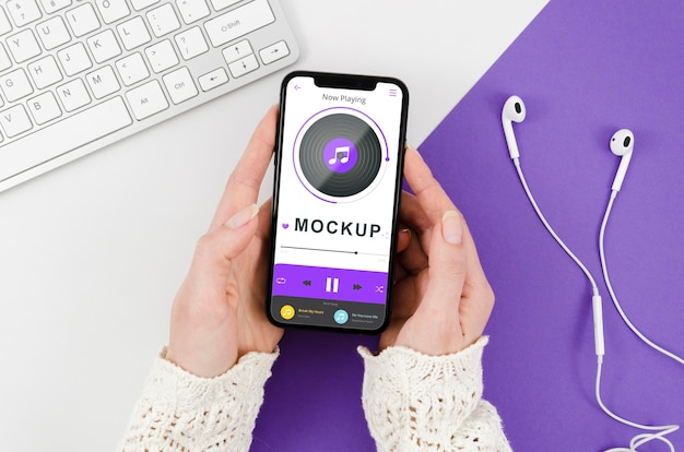 Flat lay hands holding smartphone mock-up with earphones Free Psd