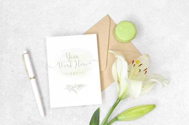 Flat lay invitation card with craft envelope, lily and macarons Premium Psd