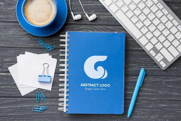 コーヒーとキーボードの近くにあるフラットレイアウトのノートブックモックアップと文房具 無料 Psd