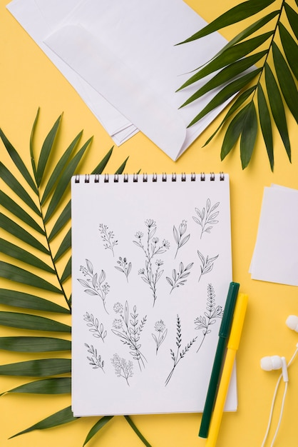 Flat lay notebook mock-up and pen near with tropical leaves Free Psd
