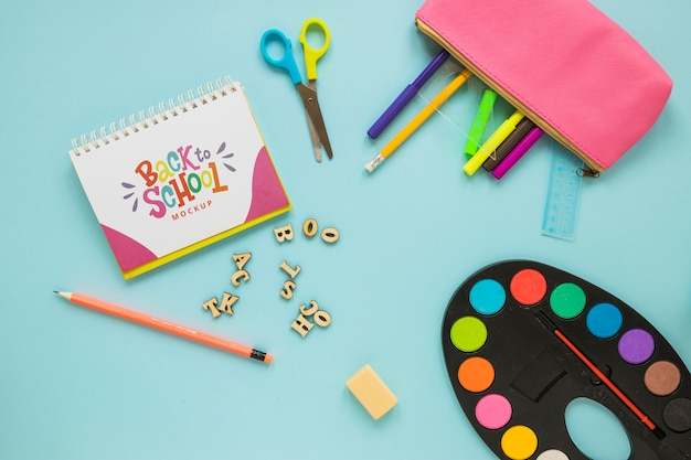 Flat lay school supplies on blue background Free Psd