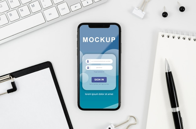 Flat lay smartphone mock-up with clipboard and pen on desk Free Psd