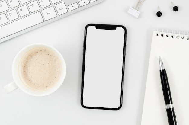 Flat lay smartphone mock-up with empty cup on desk Free Psd