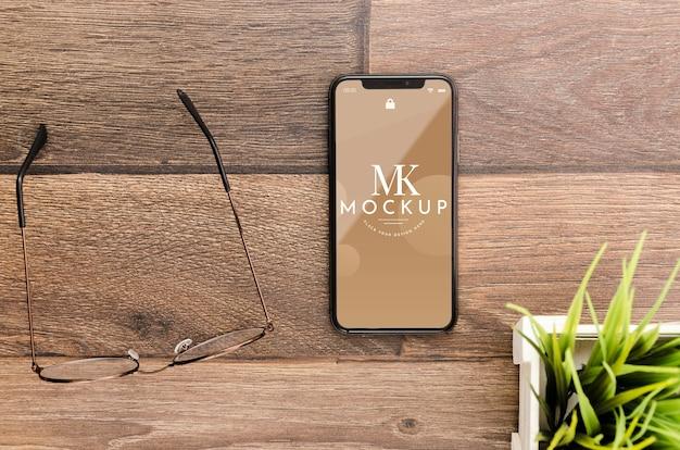 Mock-up di smartphone piatto laici con gli occhiali sulla scrivania Psd Gratuite