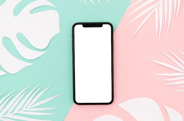 Плоский макет смартфона с листьями на столе Бесплатные Psd