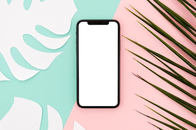 Flat lay smartphone mock-up with leaves Free Psd