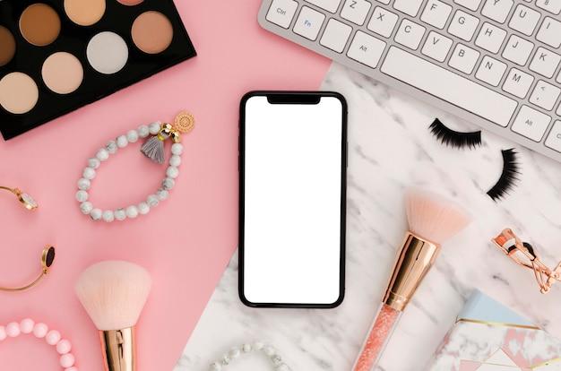 机の上の化粧ブラシ付きのフラットレイスマートフォンモックアップ 無料 Psd