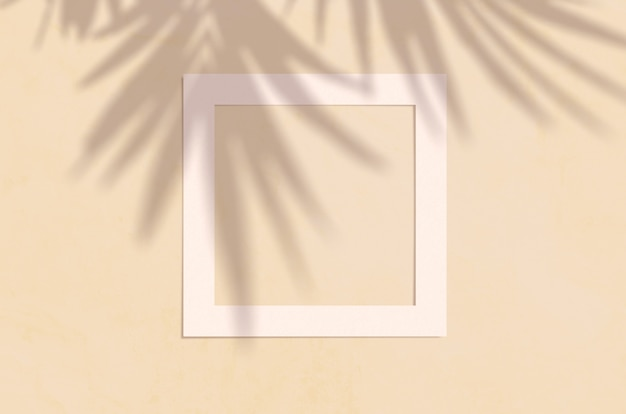 Flat lay top view of creative copyspace with paper white frame and tropical leaves palm shadow on beige color. Premium Psd