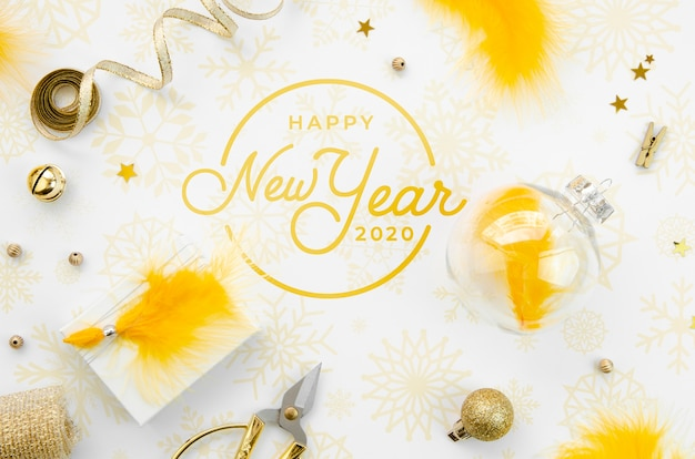 Flat lay yellow new year party accessories and happy new year lettering Free Psd