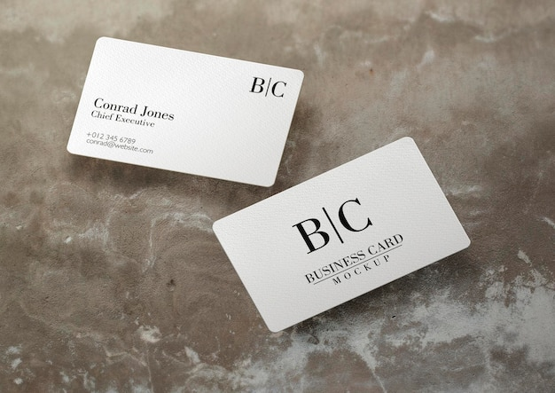 Floating business card over concrete surface mockup Free Psd