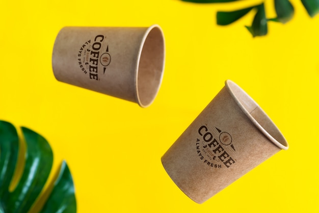 Floating eco friendly paper disposable mockup cups above yellow background with green palm leaves. z