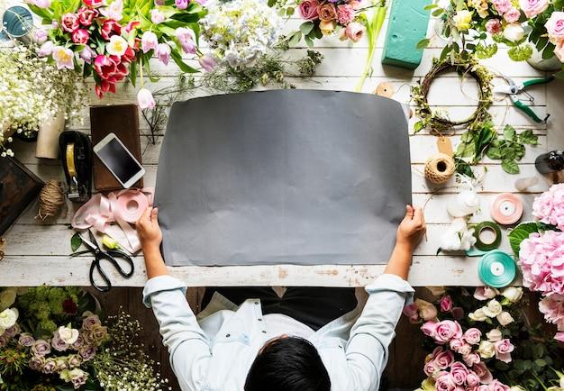 Флорист показывает пустую бумагу для дизайна пространства на деревянном столе Бесплатные Psd