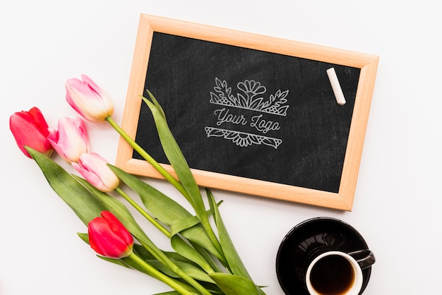 Flowers on blackboard and coffee cup Free Psd