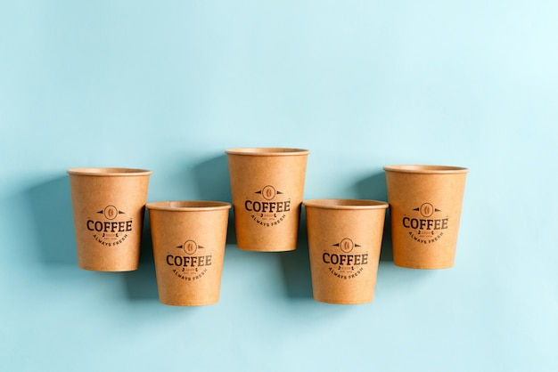 Летающие экологически чистые бумажные одноразовые чашки макета выше пастельных синем фоне. ноль отходов Premium Psd